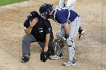 FILE - In this May 28, 2019, file photo, San Diego Padres catcher Austin Hedges, right, checks on home plate umpire Eric Cooper after the official took a foul ball from New York Yankees' DJ LeMahieu during the sixth inning of a baseball game in New York. Cooper, the Major League Baseball umpire who worked the AL Division Series two weeks ago, has died. He was 52. Commissioner Rob Manfred announced Cooper's death Sunday, Oct. 20. Cooper died after having a blood clot. (AP Photo/Julio Cortez, File)