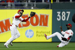 Philadelphia Phillies shortstop Sean Rodriguez, left, catches a fly out by Miami Marlins' Brian Anderson as center fielder Andrew McCutchen slides in during the fourth inning of a baseball game, Friday, April 26, 2019, in Philadelphia. (AP Photo/Matt Slocum)