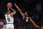 Villanova guard Phil Booth (5) puts up a shot against Xavier guard Kyle Castlin (2) during overtime of an NCAA college basketball semifinal game in the Big East men's tournament, Friday, March 15, 2019, in New York. Villanova won 71-67 in overtime. (AP Photo/Julio Cortez)