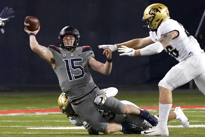 Arizona quarterback Will Plummer (15) gets pressured by Colorado safety Isaiah Lewis and Chase Newman (46) during the second half of an NCAA college football game, Saturday, Dec. 5, 2020, in Tucson, Ariz. Colorado won 24-13. (AP Photo/Rick Scuteri)