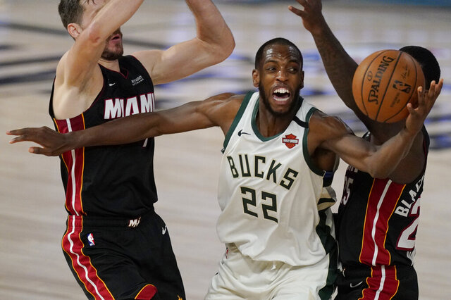 FILE - Milwaukee Bucks' Khris Middleton (22) is defended by Miami Heat's Goran Dragic, left, and Miami Heat's Kendrick Nunn, right, in the second half of an NBA conference semifinal playoff basketball game in Lake Buena Vista, Fla., in this Tuesday, Sept. 8, 2020, file photo. The Bucks paid a hefty price to acquire guard Jrue Holiday to join a nucleus that includes Giannis Antetokounmpo and All-Star forward Khris Middleton as they try to erase the postseason disappointment of the last two years. (AP Photo/Mark J. Terrill, File)