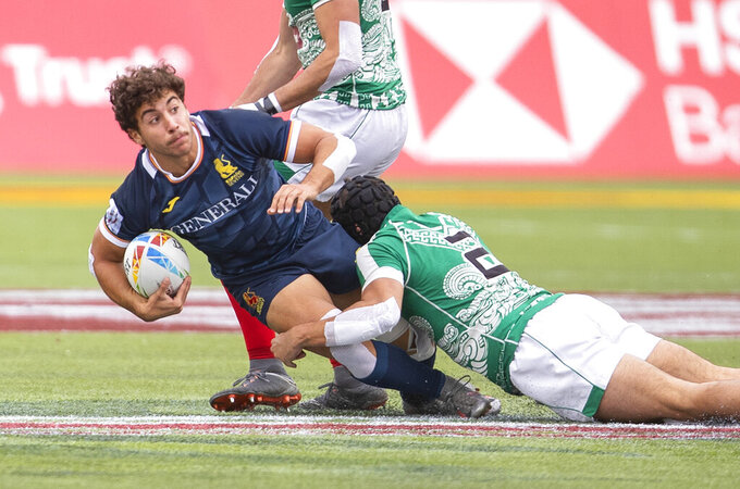 Spain's Mana Williams, left, is tackled by Mexico's Ricardo Ancira during an HSBC Canada Sevens quarterfinal rugby match in Edmonton, Alberta, Sunday, Sept. 26, 2021. (Jason Franson/The Canadian Press via AP)