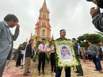 The brother of Hoang Van Tiep carries his portrait outside Trung Song church during his funeral on Thursday, Nov. 28, 2019, in Dien Chau, Vietnam. The 18-year old Tiep was among the 39 Vietnamese who died when human traffickers carried them by truck to England in October, and whose remains were among the 16 repatriated to their homeland Wednesday. (AP Photo/Hau Dinh)