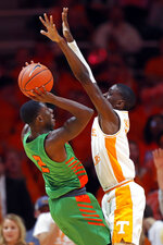 Florida A&M guard Kamron Reaves (2) tries to shoot over Tennessee guard Davonte Gaines (0) during the first half of an NCAA college basketball game Wednesday, Dec. 4, 2019, in Knoxville, Tenn. (AP Photo/Wade Payne)