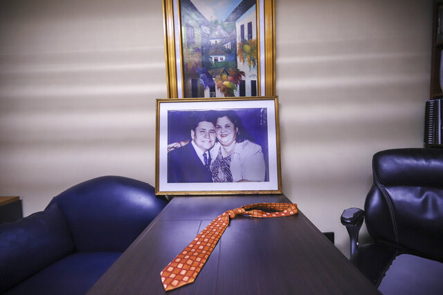 The tie belonging to the late evangelical Pastor Ovidio Valladares sits on a table in his former office, along with a portrait of him and his wife Aura Maria Valladares at Bethel evangelical church in Managua, Nicaragua, Wednesday, Aug. 12, 2020. Valladares died from COVID-19 related complications on June 5th, and more than 40 evangelical leaders have died since March from the disease nationwide. (AP Photo/Alfredo Zuniga)