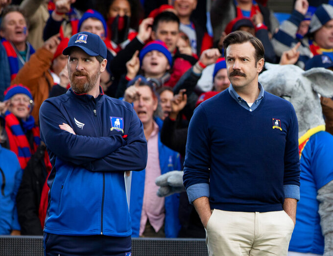 """This image released by Apple TV Plus shows Brendan Hunt, left, and Jason Sudeikis in """"Ted Lasso,"""" premiering globally on Friday, August 14. (Apple TV Plus via AP)"""
