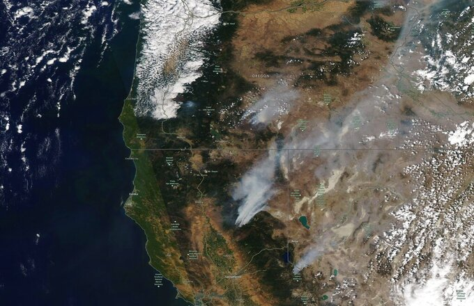This satellite image provided by Satellite image ©2021 Maxar Technologies shows the wildfires in Northern California and Oregon on Wednesday, July 21, 2021.   The Oregon fire, which was sparked by lightning, has ravaged the sparsely populated southern part of the state and had been expanding by up to 4 miles (6 kilometers) a day, pushed by strong winds and critically dry weather that turned trees and undergrowth into a tinderbox. (Satellite image ©2021 Maxar Technologies via AP)