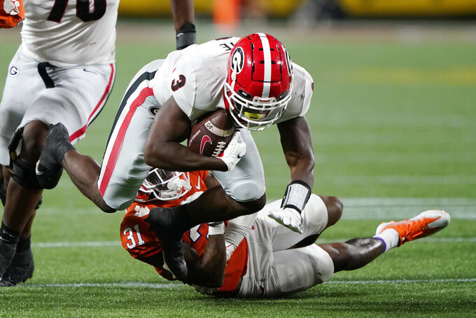 Georgia running back Zamir White, top, is tackled by Clemson cornerback Mario Goodrich during the second half of an NCAA college football game Saturday, Sept. 4, 2021, in Charlotte, N.C. (AP Photo/Chris Carlson)