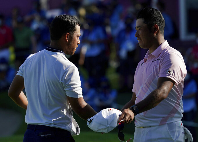 Xander Schauffele of United States, left, shakes hand with Hideki Matsuyama of Japan at the end of the third round of the men's golf event at the 2020 Summer Olympics on Saturday, July 31, 2021, in Kawagoe, Japan. (AP Photo/Matt York)