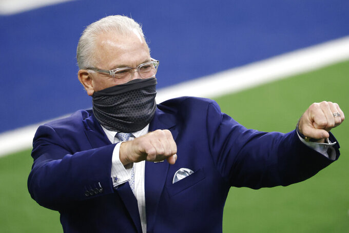 "FILE - Dallas Cowboys chief operating officer Stephen Jones gestures to fans before an NFL football game against the Cleveland Browns in Arlington, Texas, in this Sunday, Oct. 4, 2020, file photo. The Dallas Cowboys signed their star quarterback to a long-term deal, which means they won't be in the market at that position with the 10th overall pick in the NFL draft. ""Barring something very opportunistic, we certainly want to improve our defensive football team,"" executive vice president of personnel Stephen Jones said on his radio show this week. (AP Photo/Ron Jenkins, File)"