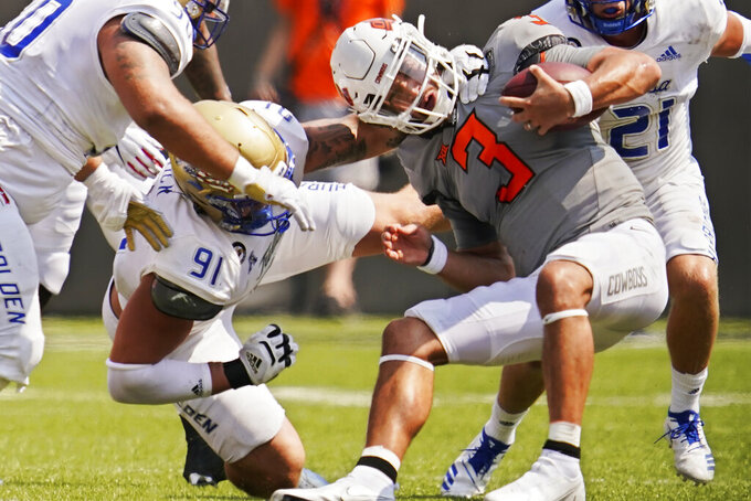 Oklahoma State quarterback Spencer Sanders (3) is tackled by Tulsa defensive lineman Cullen Wick (91) in the first half of an NCAA college football game, Saturday, Sept. 11, 2021, in Stillwater, Okla. (AP Photo/Sue Ogrocki)