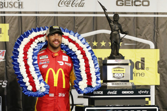 Bubba Wallace stands with the trophy after winning a NASCAR Cup series auto race Monday, Oct. 4, 2021, in Talladega, Ala. (AP Photo/Russell Norris)