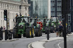 Farmers from the group Save British Farming drive tractors across Westminster Bridge, in London, in a protest against cheaply produced lower standard food being imported from the U.S. after Brexit that will undercut them, Wednesday, July 8, 2020. (AP Photo/Matt Dunham)