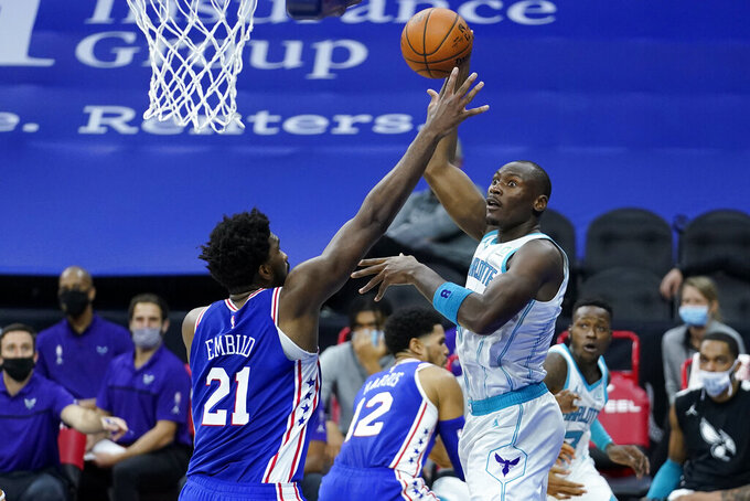 Charlotte Hornets' Bismack Biyombo, right, goes up for a shot against Philadelphia 76ers' Joel Embiid during the first half of an NBA basketball game, Monday, Jan. 4, 2021, in Philadelphia. (AP Photo/Matt Slocum)