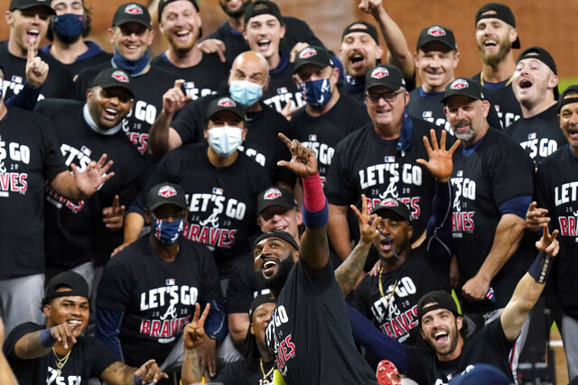 Atlanta Braves' Marcell Ozuna, front, pretends to take a selfie as he celebrates with teammates after they defeated the Miami Marlins in Game 3 of a baseball National League Division Series, Thursday, Oct. 8, 2020, in Houston. (AP Photo/Eric Gay)