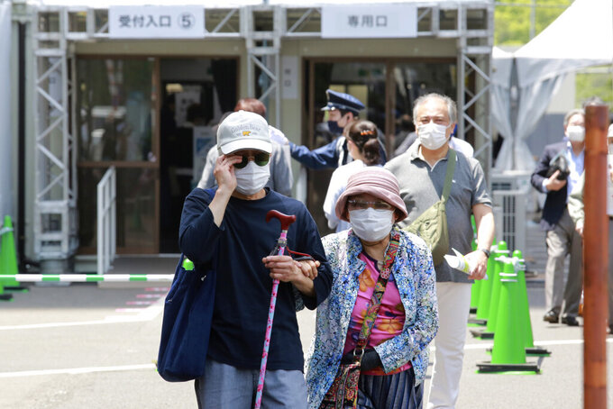 Elderly people go out of the newly-opened mass vaccination center after receiving the Moderna coronavirus vaccine in Tokyo, Monday, May 24, 2021. Japan mobilized military doctors and nurses to give shots to elderly people in Tokyo and Osaka on Monday as the government desperately tries to accelerate its vaccination rollout and curb coronavirus infections just two months before hosting the Olympics. (AP Photo/Koji Sasahara)