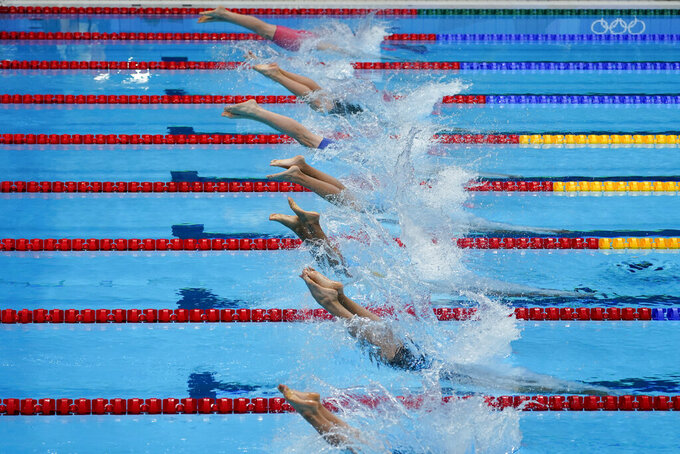Swimmers enter the water during the first heat in the men's 4x100-meter at the 2020 Summer Olympics, Sunday, July 25, 2021, in Tokyo, Japan. (AP Photo/Charlie Riedel)