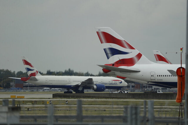 FILE - In this Monday, Sept. 9, 2019 file photo, a British Airways plane, at left, is towed past other planes sitting parked at Heathrow Airport in London. British Airways said Tuesday Nov. 17, 2020, that it will start testing passengers flying from the U.S. to London's Heathrow Airport for COVID-19 in an effort to persuade the British government it should scrap rules requiring most international travelers to quarantine for 14 days. (AP Photo/Matt Dunham, File)