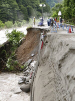 Workers attempt to restore a collapsed road as it was hit by heavy rains in Takayama, Gifu prefecture, southern Japan Thursday, July 9, 2020.  Flooding and mudslides have stranded hundreds of people in scenic hot springs and hiking areas in central Japan in the disaster that already has killed dozens of people in a southern region.(Kyodo News via AP)