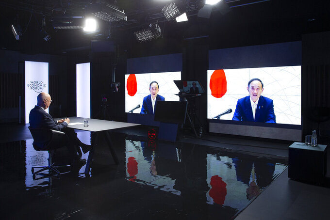 German Klaus Schwab, left, Founder and Executive Chairman of the World Economic Forum, WEF, listens Japanese Prime Minister Yoshihide Suga displayed in screens during a video conference at the Davos Agenda, in Cologny near Geneva, Switzerland, Friday, January 29, 2021. The Davos Agenda, from 25 to 29 January 2021, is a online edition due to the coronavirus disease (COVID-19) outbreak gather global leaders to shape the principles, policies and partnerships needed in this challenging new context. (Salvatore Di Nolfi/Keystone via AP)