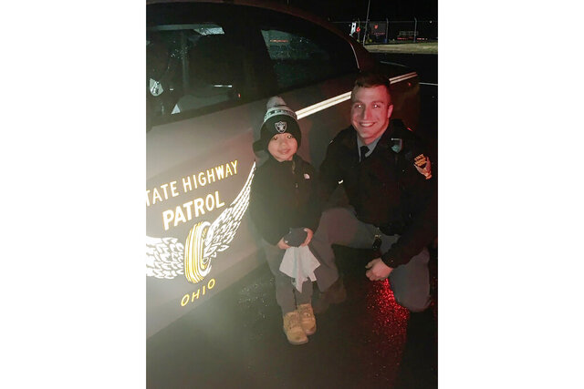 In this Sunday, Dec. 29, 2019, photo provided by Leah Sharkey, her son and the Ohio State Highway Patrol Trooper Alex Schlottag pose for a photo, west of Sandusky, Ohio. The Ohio state trooper reunited the young boy with his favorite stuffed toy,