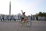 A protester rides a bicycle in front of a police during an opposition rally to protest the presidential inauguration in Minsk, Belarus, Wednesday, Sept. 23, 2020. Belarus President Alexander Lukashenko has been sworn in to his sixth term in office at an inaugural ceremony that was not announced in advance amid weeks of huge protests saying the authoritarian leader's reelection was rigged. Hundreds took to the streets in several cities in the evening to protest the inauguration. (AP Photo)