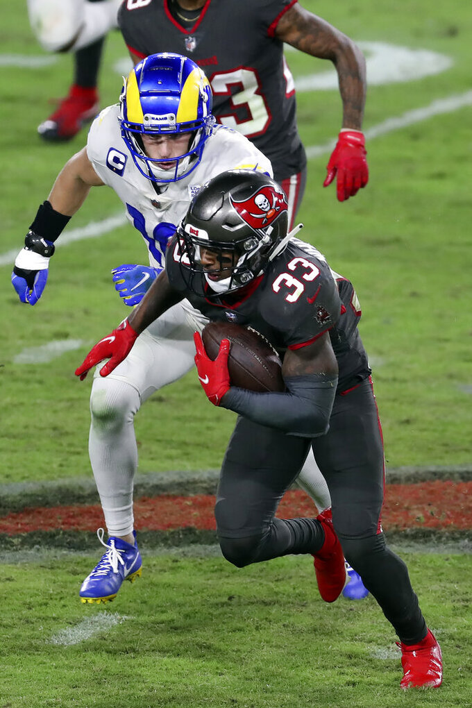Tampa Bay Buccaneers free safety Jordan Whitehead (33) runs with the football after intercepting a pass intedned for Los Angeles Rams wide receiver Cooper Kupp (10) during the second half of an NFL football game Monday, Nov. 23, 2020, in Tampa, Fla. (AP Photo/Mark LoMoglio)