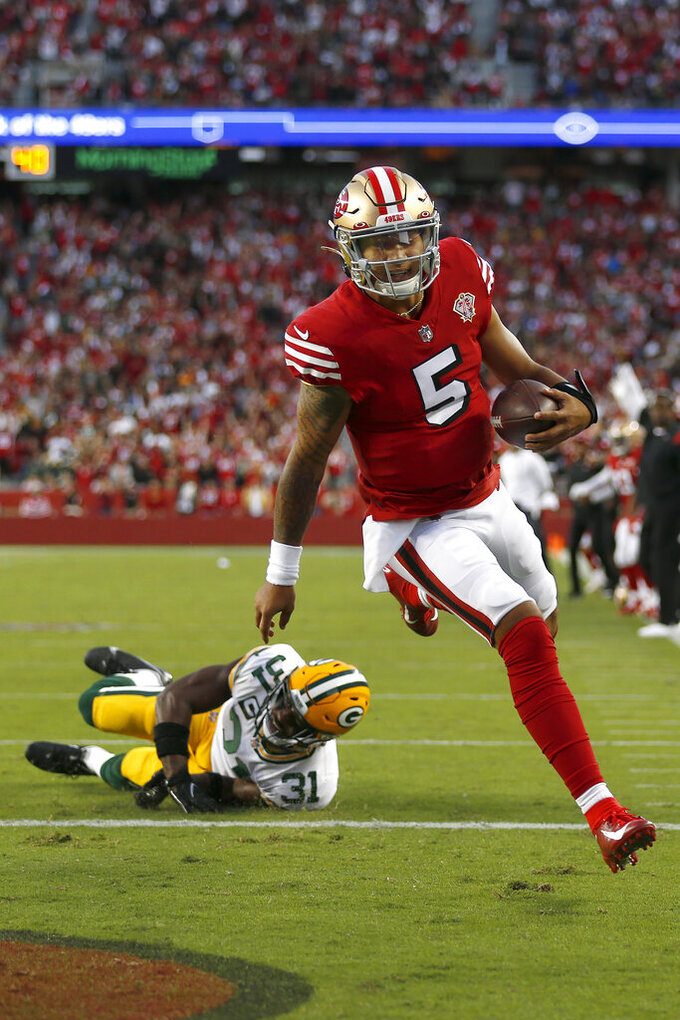 San Francisco 49ers quarterback Trey Lance (5) scores a touchdown past Green Bay Packers strong safety Adrian Amos (31) during the first half of an NFL football game in Santa Clara, Calif., Sunday, Sept. 26, 2021. (AP Photo/Jed Jacobsohn)