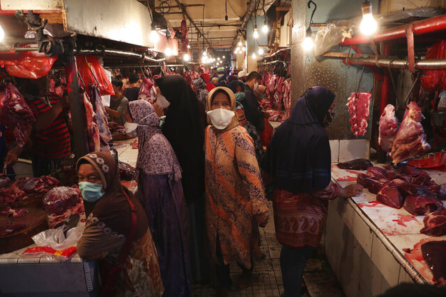 Muslim women shop for meat in preparation of the upcoming Eid al-Fitr holiday that marks the end of the holy fasting month of Ramadan amid fears of the new coronavirus outbreak at a market in Jakarta, Indonesia, Friday, May 22, 2020. (AP Photo/Achmad Ibrahim)