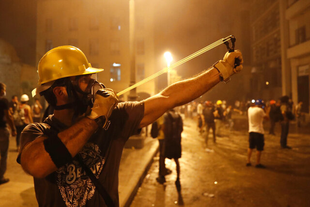 A protester uses a slingshot toward the Lebanese riot police, during anti-government protest following Tuesday's massive explosion which devastated Beirut, Lebanon, Sunday, Aug. 9. 2020. (AP Photo/Hussein Malla)