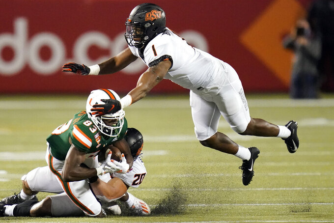 Miami wide receiver Michael Redding III (83) makes a catch as he is tackled by Oklahoma State linebacker Malcolm Rodriguez, center, and linebacker Calvin Bundage (1) during the second half of the Cheez-it Bowl NCAA college football game, Tuesday, Dec. 29, 2020, in Orlando, Fla. (AP Photo/John Raoux)