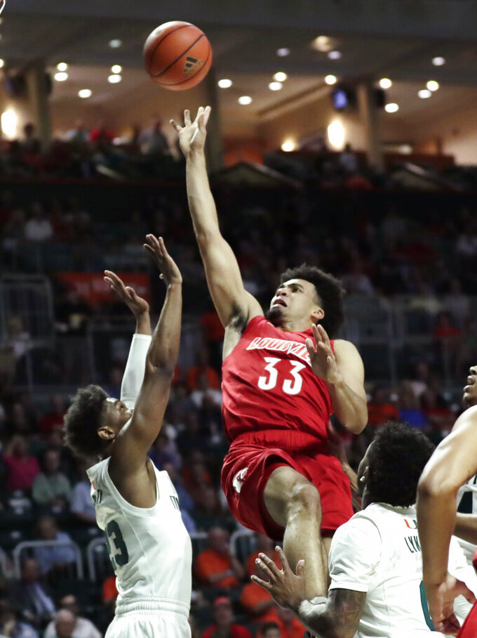 Louisville forward Jordan Nwora (33) shoots over Miami guard Kameron McGusty (23) during the first half of an NCAA college basketball game, Tuesday, Nov. 5, 2019, in Coral Gables, Fla. (AP Photo/Lynne Sladky)