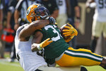 Green Bay Packers running back Aaron Jones, right, is stopped by New Orleans Saints defensive end Marcus Davenport, left, during the first half of an NFL football game, Sunday, Sept. 12, 2021, in Jacksonville, Fla. (AP Photo/Stephen B. Morton)