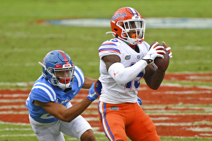 Florida wide receiver Jacob Copeland (15) catches a pass as Mississippi defensive back Deane Leonard (24) defends during the first half of an NCAA college football game in Oxford, Miss., Saturday, Sept. 26, 2020. (AP Photo/Thomas Graning)