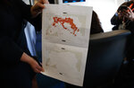 White House press secretary Sarah Sanders holds a map of Syria in the press cabin on Air Force One, Friday, March 22, 2019, on the tarmac at Palm Beach International Airport, in West Palm Beach, Fla. (AP Photo/Carolyn Kaster)