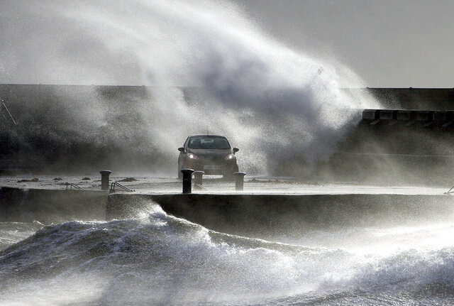 Waves lash the coast on the Ayrshire coast at Ardrossan, Scotland, Sunday, Feb. 9, 2020. Trains, flights and ferries have been cancelled and weather warnings issued across the United Kingdom and in northern Europe as the storm with winds expected to reach hurricane levels batters the region. (Andrew Milligan/PA via AP)