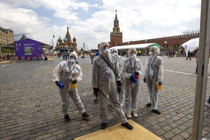 Volunteers wearing face masks, gloves and protective gear to protect against coronavirus, gather to clean an area of an outdoor book market set up at Red Square with GUM, State Department store, left, St. Basil's Cathedral, center, Spasskaya Tower, second with, and the Kremlin Wall, right, in Moscow, Russia, Saturday, June 6, 2020. Muscovites clad in face masks and gloves ventured into Red Square for an outdoor book market, a small sign of the Russian capital's gradual efforts to open up amid coronavirus concerns. (AP Photo/Alexander Zemlianichenko)