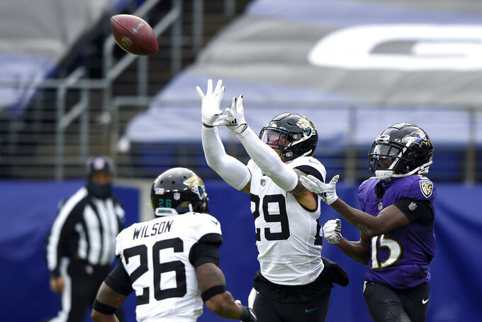 Jacksonville Jaguars safety Josh Jones (29) prepares to intercept a pass from Baltimore Ravens quarterback Lamar Jackson, not visible, intended for wide receiver Marquise Brown (15) prior to an NFL football game, Sunday, Dec. 20, 2020, in Baltimore. Jaguars safety Jarrod Wilson (26) looks on. (AP Photo/Gail Burton)