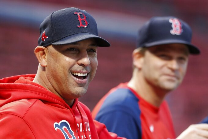 Boston Red Sox manager Alex Cora watches the team's baseball workout with bench coach Tim Hyers, right,  Saturday, Oct. 9, 2021, in Boston. The Red Sox hosts the Tampa Bay Rays in Game 3 of the American League Division Series on Sunday. (AP Photo/Michael Dwyer)