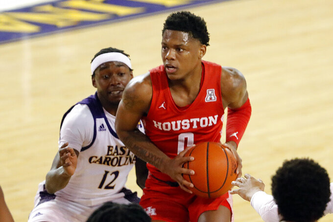 Houston's Marcus Sasser (0) drives the ball past East Carolina's Tremont Robinson-White (12) during the first half of an NCAA college basketball game in Greenville, N.C., Wednesday, Feb. 3, 2021. (AP Photo/Karl B DeBlaker)