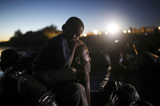 FILE - In this Thursday, Sept. 23, 2021 file photo, migrants, most from Haiti, cross the Rio Grande towards Del Rio, Texas, from Ciudad Acuña, Mexico. Faith-based groups — many of them longtime advocates for a more welcoming immigration policy -- have been scrambling to keep up with fast-paced developments in the Haitian migrant crisis, trying to assist those in need while assailing the harsh Border Patrol tactics employed against them. (AP Photo/Felix Marquez)