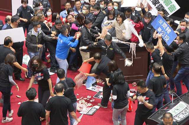 "In this image made from video, lawmakers fight during a parliament session in Taipei, Taiwan, Friday, Nov. 27, 2020. Taiwan's lawmakers got into a fist fight and threw pig guts at each other Friday over a soon-to-be enacted policy that would allow imports of U.S. pork and beef. A blue banner at right reads: ""Protest against ractopamine pork, We want a referendum."" (FTV via AP)"