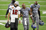 Tampa Bay Buccaneers quarterback Tom Brady (12) and Detroit Lions running back Adrian Peterson (28) walk off the field after their NFL football game, Saturday, Dec. 26, 2020, in Detroit. (AP Photo/Al Goldis)