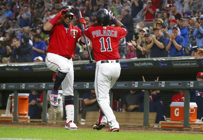Minnesota Twins' Jorge Polanco, right celebrates his solo home run off Texas Rangers pitcher Adrian Sampson with Nelson Cruz during the second.inning of a baseball game Friday, July 5, 2019, in Minneapolis. (AP Photo/Jim Mone)