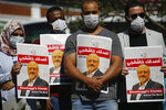 People hold posters of slain Saudi journalist Jamal Khashoggi, near the Saudi Arabia consulate in Istanbul, marking the two-year anniversary of his death, Friday, Oct. 2, 2020. The gathering was held outside the consulate building, starting at 1:14 p.m. (1014 GMT) marking the time Khashoggi walked into the building where he met his demise. (AP Photo/Emrah Gurel)