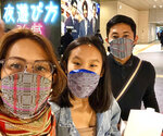 In this late February 2020, photo, Carlo Navarro poses behind wife Evie and daughter Gia for a family photo while wearing face masks during a trip to Tokyo. Days after he was cleared and discharged from hospital, Carlo Navarro shared his COVID-19 experience on a Facebook public post. (Carlo Navarro via AP)