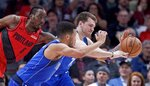 Dallas Mavericks forward Luka Doncic, right, and guard Jalen Brunson, center, reach for a loose ball in front of Portland Trail Blazers forward Al-Farouq Aminu during the first half of an NBA basketball game in Portland, Ore., Wednesday, March 20, 2019. (AP Photo/Craig Mitchelldyer)