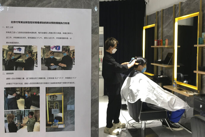 A barber cuts a client's hair near a disinfection notice at a hair salon in Beijing, Monday, Feb. 24, 2020. Monday is the second day of the second month of the Chinese lunar calendar, traditionally an auspicious time when people rush into barbershops to get new haircuts. Getting a fresh look on the day is thought to bring good luck for the year ahead, but getting a haircut has become a challenge in China now that most barbershops are temporarily shut to avoid public gatherings amid the virus outbreak. (AP Photo/Olivia Zhang)