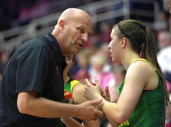 Oregon head coach Kelly Graves, left, talks with guard Sabrina Ionescu (20) on the bench during the second half  in an NCAA college basketball game against Stanford, Sunday, Feb. 10, 2019, in Stanford, Calif. Oregon won 88-48. (AP Photo/Tony Avelar)
