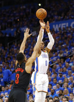 Oklahoma City Thunder guard Russell Westbrook (0) shoots a three point basket as Portland Trail Blazers guard CJ McCollum (3) defends in the first half of Game 4 of an NBA basketball first-round playoff series Sunday, April 21, 2019, in Oklahoma City. (AP Photo/Alonzo Adams)